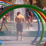 A young boy pauses after walking through a series of water hoops