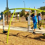 A child uses his hands to hang from a play structure