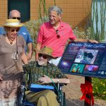 Howard Israel poses near solar walk sign
